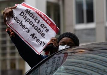 Chicago teachers have voted to accept an agreement for returning to in-person classes in the coming weeks. Here, a woman holds a sign at a car caravan in support of teachers' call for more safety precautions.