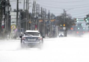 Vehicles drive on snow and sleet-covered roads Monday, in Spring, Texas. Texas Gov. Greg Abbott issued a disaster declaration in all of the state's 254 counties.