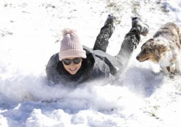 Megan Pennartz and her dog Jensen go sledding in Fort Worth, Texas, on Monday.