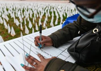 """Patrice Howard writes on white flags before planting them to remember her recently deceased father and close friends in November at """"IN AMERICA How Could This Happen...,"""" a public art installation in Washington, D.C. Led by artist Suzanne Firstenberg, vo"""