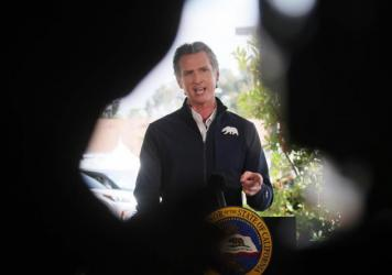 California Governor Gavin Newsom speaks at a press conference following the opening of a new large scale COVID-19 vaccination site in Los Angeles on Tuesday. Newsom says the state will start setting aside 10% of its vaccine allotment for teachers, day ca