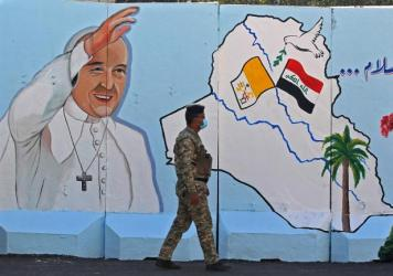 An Iraqi policeman walks by a mural depicting Pope Francis on the outer walls of Our Lady of Salvation Church in Baghdad on Monday. Pope Francis' visit from March 5 to 8 will include trips to Baghdad, the city of Mosul and a meeting with the country's to