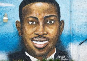 """A mural depicting Ahmaud Arbery in July 2020 in Brunswick, Ga. Gregory McMichael, Travis McMichael and William """"Roddie"""" Bryan are facing murder charges in connection with his death."""