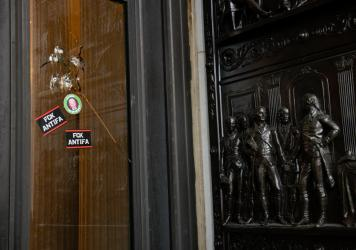 "Stickers reading ""Fck Antifa"" are stuck on a broken window at the U.S. Capitol after the building was breached by rioters on Jan. 6."