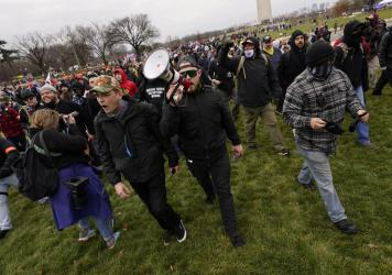 Prosecutors say Ethan Nordean, seen with a bullhorn, led members of the far-right group the Proud Boys in the Jan. 6 riot. He faces federal charges, but will be released from custody while he awaits trial.