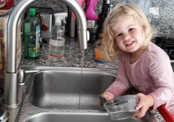 The author's daughter, Rosy, at age 2 as she does dishes — voluntarily. Getting her involved in chores did lead to the kitchen being flooded and dishes being broken. But she is still eager to help.