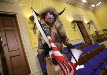 "Jacob Chansley, photographed during the Jan. 6 U.S. Capitol insurrection, screams ""Freedom"" inside the Senate chamber following the breach of a mob during a joint session of Congress."