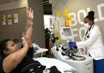Melissa Cruz elevates her arm after donating COVID-19 convalescent plasma in April 2020 as phlebotomist Jenee Wilson shuts down the collection equipment at Bloodworks Northwest in Seattle.
