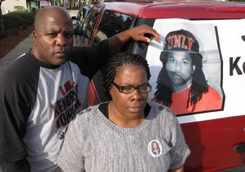 """Kenneth and Jacquelyn Johnson stand next to a banner on their SUV showing their late son Kendrick, in Valdosta, Ga., in December 2013. A family spokesperson told NPR they are """"cautiously optimistic"""" after the Lowndes County Sheriff's Office reopened its"""