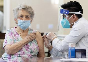 A CVS pharmacist gives the Pfizer/BioNTech COVID-19 vaccine to a resident at the Emerald Court senior living community in Anaheim, Calif., in January. Federal health officials have revised advice on nursing home visitations for the first time since Septe