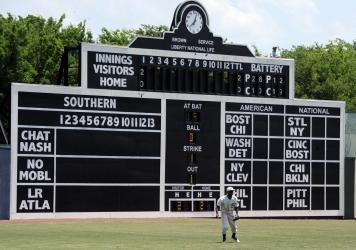Birmingham Barons outfielder Luis Basabe moves toward a ball in front of the vintage scoreboard in 2019 at Rickwood Field, America's oldest baseball park, in Birmingham, Ala.