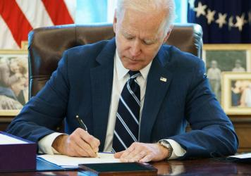 President Biden signs the American Rescue Plan on March 11 in the Oval Office. The $1.9 trillion economic stimulus bill includes $1,400 stimulus checks for most Americans.