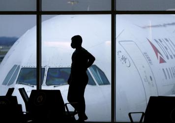 Friday marked the busiest day for the nation's airports since the start of the pandemic in March 2020. Above, a passenger wears a face mask as he waits for a Delta Airlines flight at Hartsfield-Jackson International Airport in Atlanta on Feb. 18, 2021.