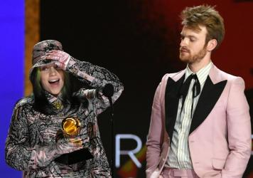 """Billie Eilish (left) and FINNEAS accept the Record of the Year award for Eilish's song """"Everything I Wanted"""" during the 63rd annual Grammy Awards on Sunday."""