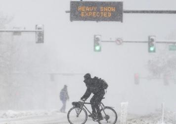 People cross the road as a sign warns of heavy snow on Sunday in Denver, Colo. A winter storm closed roads, impacted flights, and knocked out power in Arizona, Wyoming, Nebraska, and Colorado through the weekend.