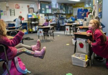 "Two first grade students talk in the back of class at the Green Mountain School last month in Woodland, Wash. The CDC's current guidance for schools recommends seating or desks be ""at least 6 feet apart when feasible."""