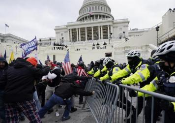 In January, rioters, including many with ties to white supremacists, try to break through a police barrier at the Capitol in Washington.
