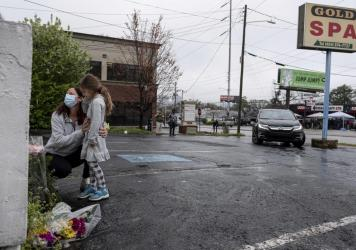 Mallory Rahman and her daughter Zara Rahman, 4, bring flowers to the Gold Spa in Atlanta on Wednesday, the day after eight people were killed at three massage spas in the Atlanta area. Authorities have arrested Robert Aaron Long, 21, in the shootings in