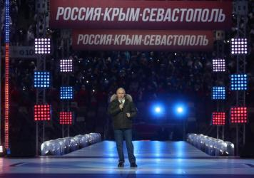 """Russian President Vladimir Putin speaks Thursday prior to a concert marking the seventh anniversary of the annexation of Crimea from Ukraine. The banner behind him reads: RUSSIA-CRIMEA-SEVASTOPOL."""""""