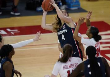 Connecticut guard Saylor Poffenbarger (4) is defended by St. John's guard Danaijah Williams (24) and forward Cecilia Holmberg (11) during the fourth quarter of an NCAA college basketball game in New York last month. The women's NCAA championship begins S