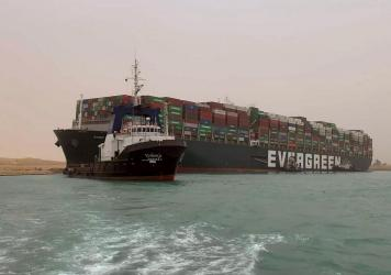A boat navigates in front of a massive cargo ship that sits grounded after it turned sideways in Egypt's Suez Canal, blocking traffic in a crucial East-West waterway for global shipping. An Egyptian official warned Wednesday it could take at least two da