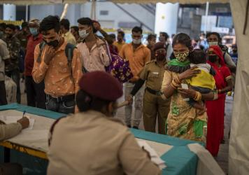 Passengers register at a counter before being tested for COVID-19 at a bus terminal on Wednesday in New Delhi.