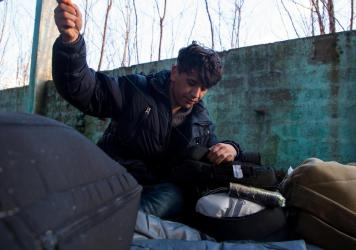 """Afghan Morteza Mohammadi, 21, sews his backpack in the ruins of the former Krajina Metal factory. He prepares for an attempt to cross into European Union members Croatia, Slovenia and Italy. Migrants and refugees here refer to the trip as """"the game."""""""