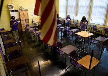 Students stand for the Pledge of Allegiance as they return to in-person learning at St. Anthony Catholic High School in California on March 24. Masks and physical distancing are proving to have some major public health benefits, keeping people from getti