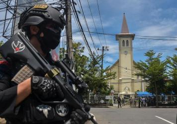 A police officer stands guard outside the Sacred Heart of Jesus Cathedral in Makassar, Indonesia, on Sunday. Two suicide bombers attacked the Roman Catholic compound, injuring at least 20 people.