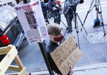 A man holds a sign after an Asian American anti-violence press conference Tuesday outside the building where a 65-year-old Asian woman was  attacked in New York City. Police said Wednesday that Brandon Elliot, 38, had been arrested and charged with crime