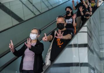 "Former lawmaker Cyd Ho (left) and pro-democracy activist Lee Cheuk-yan (center) gesture a protest slogan, ""Five demands, not one less,"" as they leave West Kowloon court in Hong Kong on Thursday after being found guilty of organizing an unauthorized assem"
