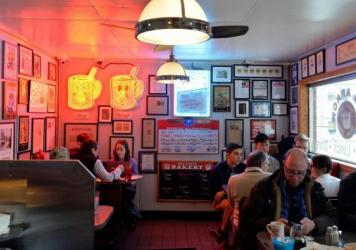 Diners sit at the 24-hour restaurant the Red Arrow Diner in Manchester, N.H., on Feb. 8, 2020. Today's diner scenes often involve masks and spaced out tables, but we're getting closer to some sense of normal returning. What questions do you have about re