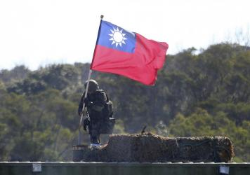 A soldier holds a Taiwanese flag during a military exercise in Hsinchu County, northern Taiwan, in January. Taiwanese troops using tanks, mortars and small arms staged a drill aimed at repelling an attack from China.