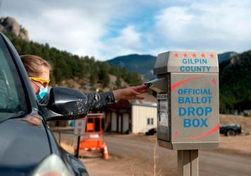 A voter drops off her ballot for the U.S. presidential election in November, in Rollinsville, Colo. Colorado's voting laws got fresh attention this week after the MLB decided to move its All-Star game to the state to protest Georgia's new legislation.
