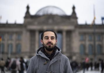 Tareq Alaows stands in front of the Bundestag, Germany's parliament, in Berlin. Alaows came to Germany as an asylum-seeker from Syria in 2015. He launched a campaign to run in Germany's federal election in September for the Green Party but recently withd