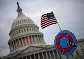 Supporters of then-President Donald Trump fly a U.S. flag with a symbol from the QAnon conspiracy theory as they gather outside the Capitol on Jan. 6 ahead of the insurrection.