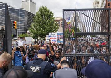 Protesters gather outside the entrance to a rally for then-President Donald Trump in June in Tulsa, Okla. A new state law increases penalties for protesters who block public roadways and grants legal immunity to drivers who unintentionally harm them as t