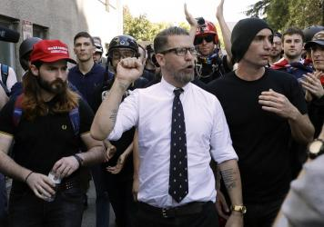"""In this 2017 photo, Gavin McInnes (center), founder of the far-right extremist group known as the Proud Boys, is surrounded by supporters after speaking at a rally in Berkeley, Calif. McInnes told NPR that the group is made up of """"funny dudes, not Nazis."""