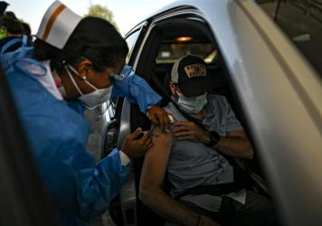 A man receives a dose of the AstraZeneca COVID-19 vaccine at the Rommel Fernández Stadium in Panama City, Panama. In the absence of Food and Drug Administration authorization, the U.S. government has been sitting on a stockpile of doses.