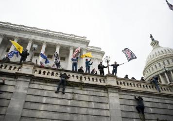 Supporters of former President Donald Trump climb the west wall of the the U.S. Capitol on Jan. 6. A New York man who was not at the riot is on trial for allegedly threatening to kill members of Congress in media posts supportive of the assault.