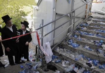 Ultra-Orthodox Jews look at the scene where dozens of people were killed and some 150 injured in a stampede during the Lag BaOmer festival at Mount Meron in northern Israel on Friday.