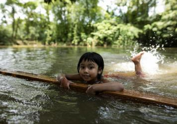 A child learns to swim in a pond in a rural area of Bangladesh.