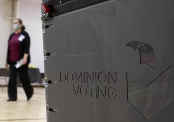 A worker passes a Dominion Voting Systems ballot scanner during Georgia's runoff Senate elections in January in Gwinnett County outside Atlanta. Former President Donald Trump and his allies spread falsehoods about the company's role in the 2020 election,