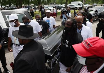Pallbearers carry Brown's casket to a horse-drawn carriage before his funeral service Monday at the Fountain of Life Church in Elizabeth City, N.C.