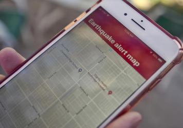 A mobile phone customer in Los Angeles looks at an earthquake warning application on an iPhone. An earthquake early warning system operated by the U.S. Geological Survey has been activated in Oregon, California and now Washington.