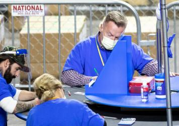 Contractors working for the firm Cyber Ninjas, which was hired by the Republican-led Arizona state Senate, count Maricopa County ballots from the 2020 general election at Veterans Memorial Coliseum on Saturday in Phoenix.
