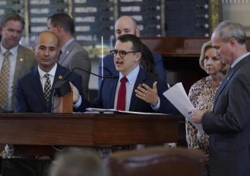 Republican state Rep. Briscoe Cain (center) stands with co-sponsors as he speaks in favor of the election bill Thursday in the House chamber at the Texas Capitol in Austin.
