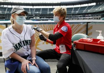 Sydney Porter of Bellevue, Wash., receives her COVID-19 vaccination from Kristine Gill, with the Seattle Fire Department's Mobile Vaccination Teams, before the game between the Seattle Mariners and the Baltimore Orioles at T-Mobile Park on May 5 in Seatt