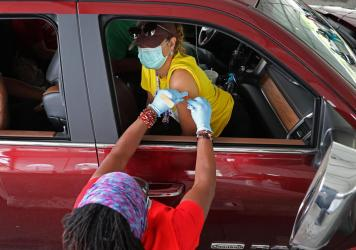 People who need help getting to a vaccination site will be able to get free or discounted rides through Uber and Lyft, the White House says. Here, a woman receives her first dose of the Pfizer vaccine at a mass vaccination site in Aberdeen, Md., after ge