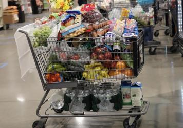 A shopper's cart is full in the checkout line at a ShopRite supermarket in April 2020 in Plainview, N.Y. A year later, prices for most goods have jumped, according to government data, as companies struggle to secure critical raw materials amid supply con